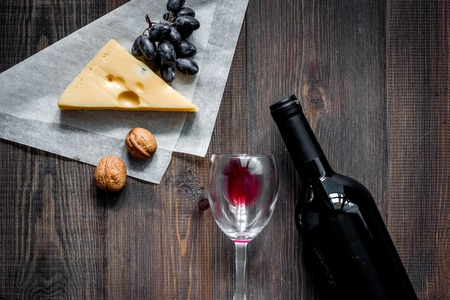 Wine snack. Cheese, nuts, grape on dark wooden table background top view copyspace