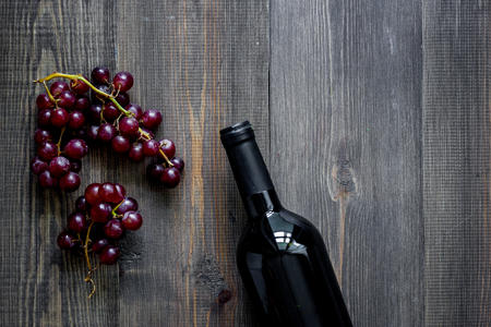 Bottle of wine and grape on dark wooden table background top view.
