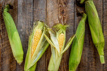 Fresh corn on rustic wooden table top view copyspace