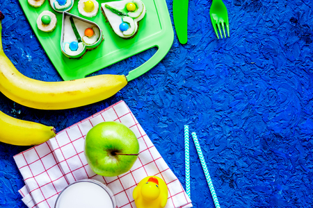 Fuit snack for clildren. Fruits and milk on blue table background top view.