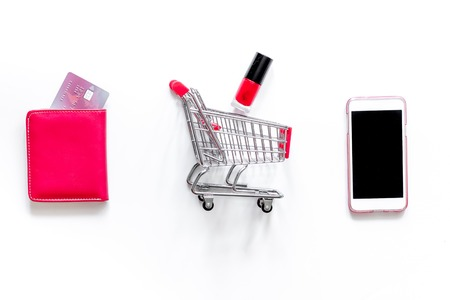Mobile shopping. Shopping cart, phone, gift box on white background top view.