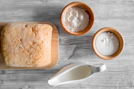bakery products: Make bread. Loaf and ingredients on light wooden table background top view.