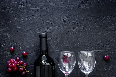 Wine glasses and bottle on black stone table background top view copyspace