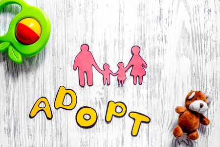 Adopt word, paper silhouette of family and toys on light wooden table background top view. 版權商用圖片 - 83217314