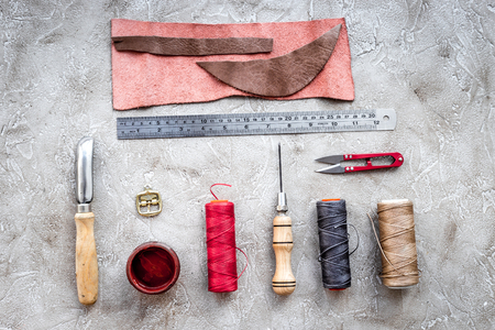 Leather workshop. Tanners tools on grey stone background top view.
