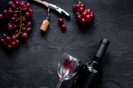 Open wine. Bottle and corkscrew on black stone table background top view.