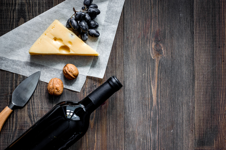 Wine snack. Cheese, nuts, grape on dark wooden table background top view Stock Photo
