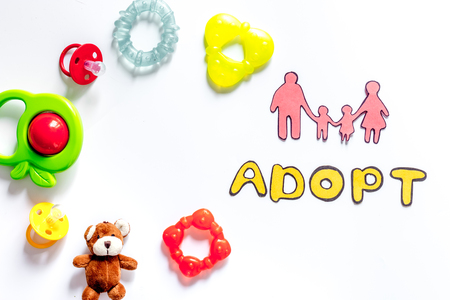 Adopt word, paper silhouette of family and toys on white background top view copyspace