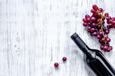 Bottle of wine and grape on light wooden table background top view copyspace.