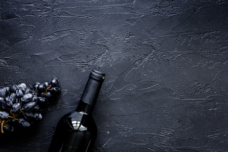 Bottle of wine and grape on black stone table background top view copyspace