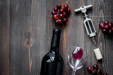 Open wine. Bottle and corkscrew on dark wooden table background top view.