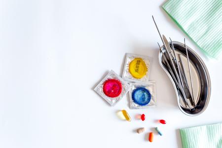 Bezoek de uroloog. Hulpmiddelen en condooms op witte achtergrond bovenaanzicht.