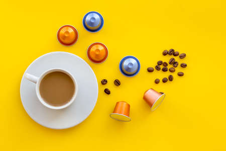 Beverage capsules for coffee mashine near coffee cup on yellow background top view.
