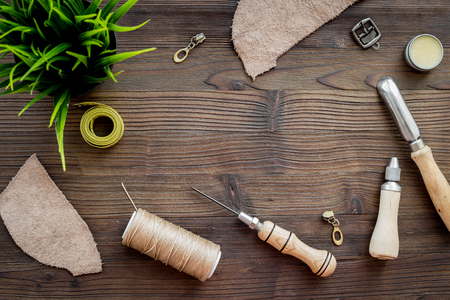 Leather craft. Tanners tools on dark wooden table background top view.