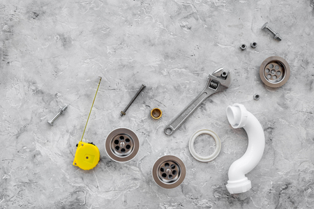 Drain parts and plumbing tools on grey stone background top view. Stock fotó - 83339769