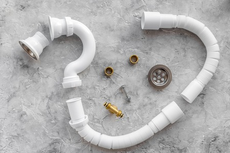 Disassembled sink drain pipe on grey stone background top view.