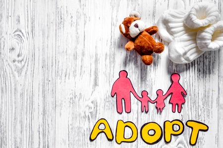 Adopt word, paper silhouette of family and toys on light wooden table background top view. Stock Photo