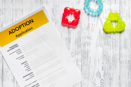 Adoption application near toy on light wooden table background top view.