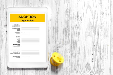Adoption application on light wooden table background top view. 版權商用圖片 - 83338895