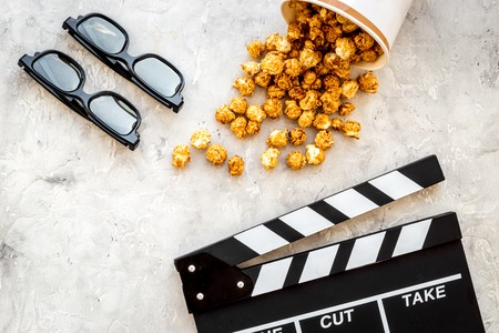 filmmaker: Watching film. Clapperboard, glasses and popcorn on grey stone background top view.