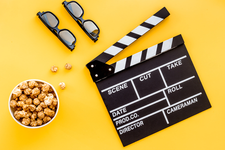 filmmaker: Watching film. Clapperboard, glasses and popcorn on yellow background top view.