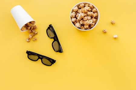 filmmaker: Watching film. Clapperboard and popcorn on yellow background top view copyspace