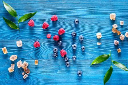 Preparing raspberry jam. Berries and sugar on blue wooden background top view