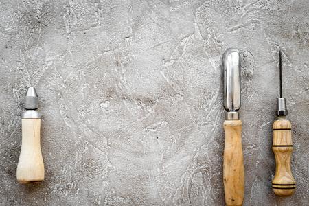Leather craft tools on grey stone background top view copyspace Zdjęcie Seryjne