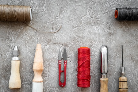Leather craft tools on grey stone background top view copyspace Stock Photo