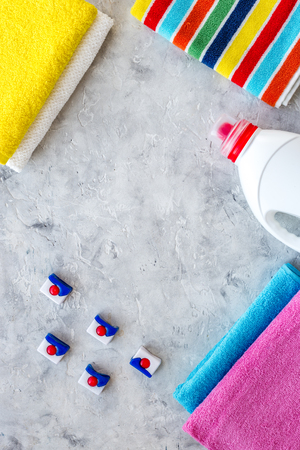 Laundry. Dry and liquid detergents near clean towel on grey stone background top view copyspace