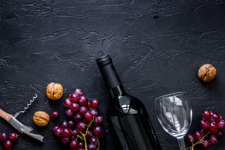 ワインを提供してください。ボトル、グラス、ナッツ、黒いテーブル背景上にブドウを表示 copyspace 写真素材