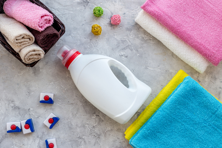 Housework. Wash clothes. Dry and liquid detergents near clean towel on grey stone background top view Stock Photo