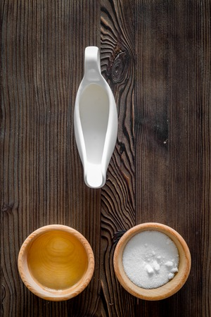 bakery products: Put the dough. Flour, oil, milk on dark wooden table background top view copyspace Stock Photo