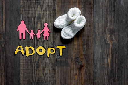 Adopt word, paper silhouette of family on dark wooden table background top view. 版權商用圖片 - 83461004