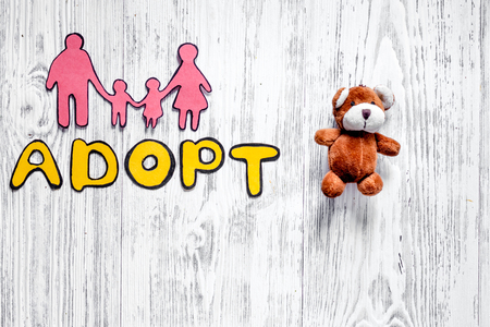 Adopt word, paper silhouette of family and toys on light wooden table background top view copyspace Stock Photo