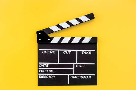 Filmmaker profession. Clapperboard on yellow background top view copyspace Foto de archivo