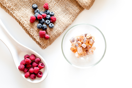 Making summer preserve. Raspberry, blueberry and sugar on white background top view copyspace