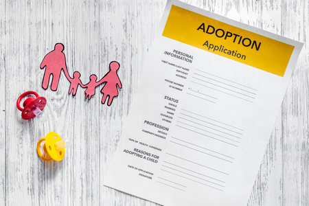 Adoption application near paper silhouette of family on light wooden table background top view Stock Photo