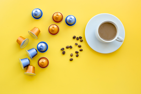 Beverage capsules for coffee mashine near coffee cup and grains on yellow background top view copyspace