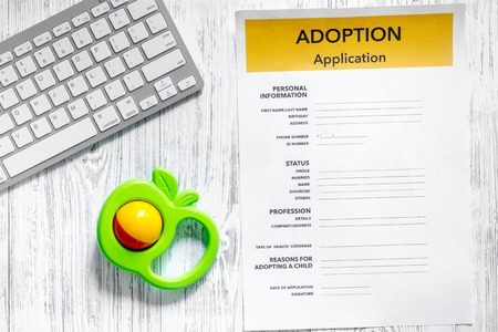 Adoption application near keyboard and toy on light wooden table background top view copyspace 版權商用圖片 - 83464941