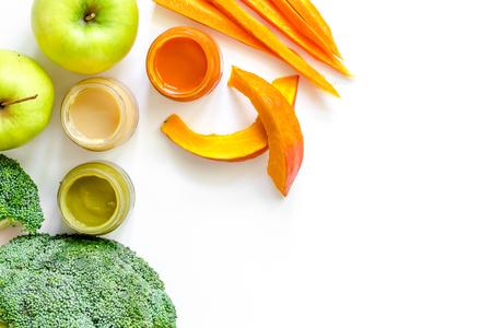 Preparando comida para bebé. Brócoli, calabaza, puré de manzana en el fondo blanco vista superior copyspace Foto de archivo - 83464636
