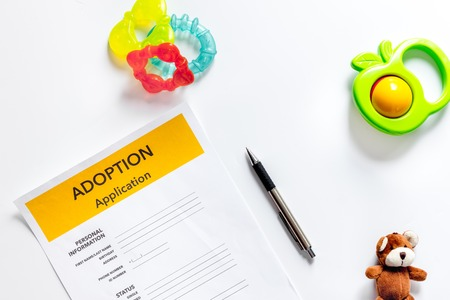 Adoption application near paper silhouette of family and toys on white background top view copyspace 版權商用圖片 - 83464637