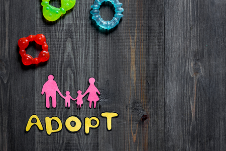 Adopt word, paper silhouette of family and toys on dark wooden table background top view copyspace