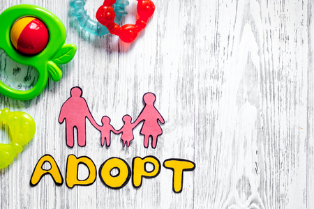 Adopt word, paper silhouette of family and toys on light wooden table background top view copyspace 版權商用圖片