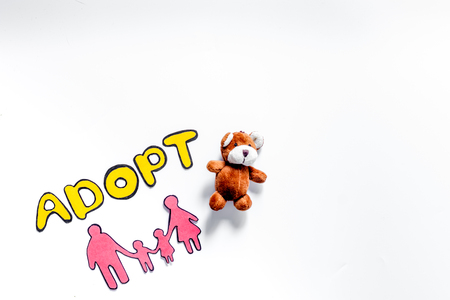 Adopt word, paper silhouette of family and toys on white background top view copyspace 版權商用圖片 - 83531325