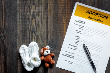 Adoption application near toy and booties on dark wooden table background top view copyspace