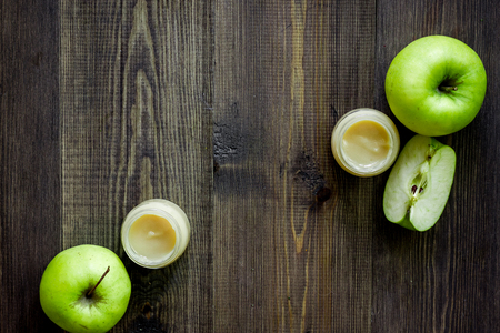Apple puree for baby on dark wooden table background top view copyspace