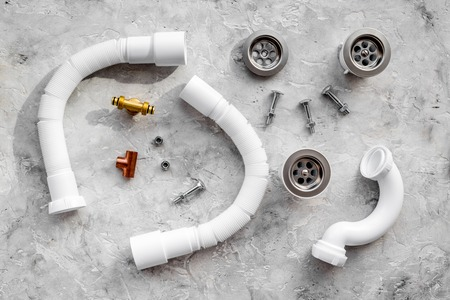 Disassembled sink drain pipe on grey stone
