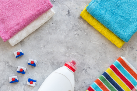 Dry and liquid detergents near clean towel on grey stone table