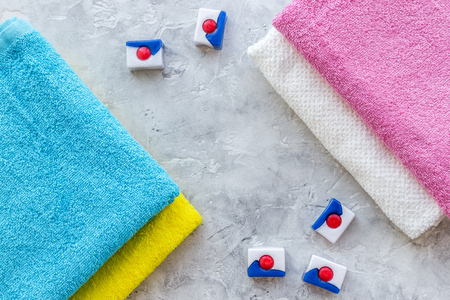 Bars of dry detergent near clean towel on grey stone table Stock Photo